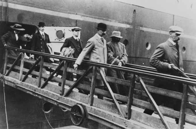 Crippen in cuffs being led from the ship by Dew